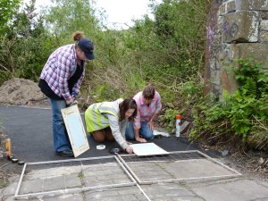 A GGAT archaeologist teaching the volunteers how to use a planning frame